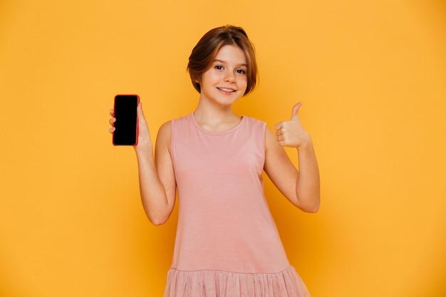 Schönes mädchen im rosa kleid, das den smartphone und daumen oben lokalisiert zeigt