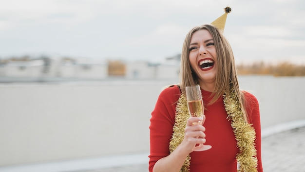 Schönes mädchen im roten kleid lachend auf dem dach mit einem glas champagner