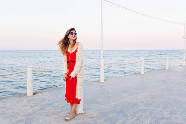 Schönes mädchen im roten kleid und in der weißen jacke steht auf einem pier, lächelt und hört musik auf kopfhörern auf einem smartphone