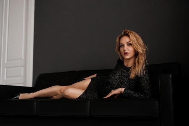 Schönes mädchen im schwarzen kleid liegt auf dem luxuskonzept der schwarzen couch