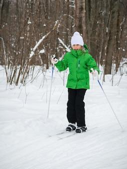 Schönes mädchen im skianzug und im weißen hut auf den skiern im wald.