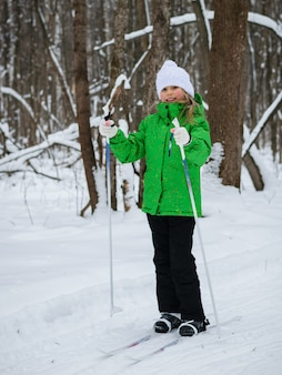 Schönes mädchen im skianzug und im weißen hut auf den skiern im winterwald.