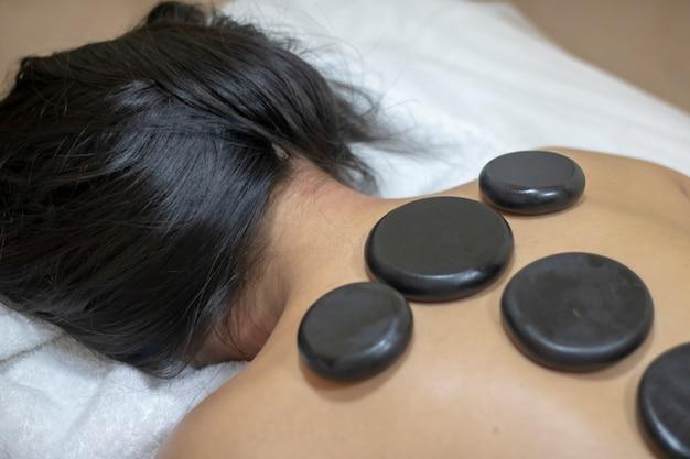 Schönes mädchen im spa auf massage mit schwarzen steinen auf ihrem rücken.