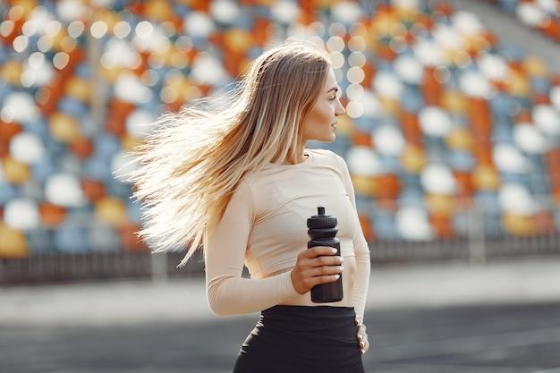 Schönes mädchen im stadion. sportmädchen in einer sportbekleidung. frau mit flasche wasser.