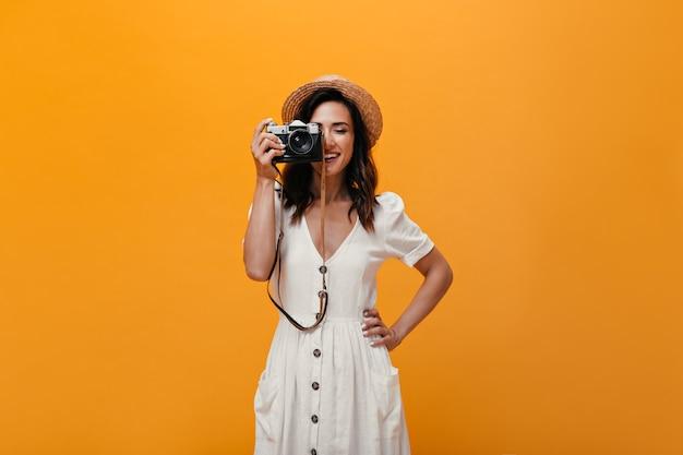 Schönes mädchen im stilvollen sommeroutfit macht bild auf retro-kamera. modische frau im weißen langen kleid und im lächelnden hut.