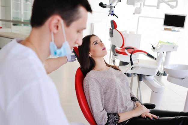Schönes mädchen im stuhl des zahnarztes