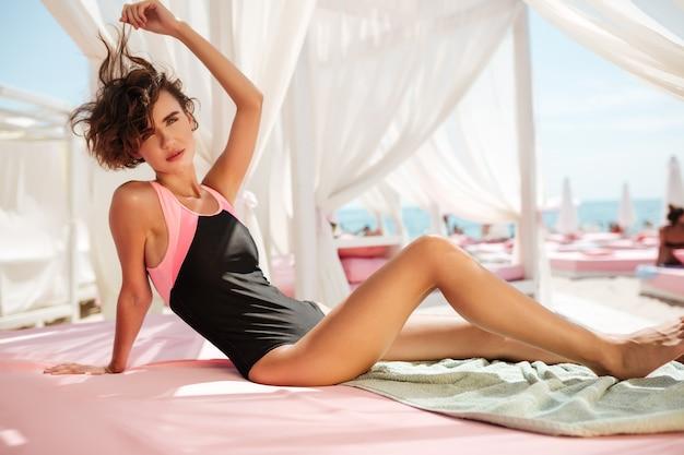Schönes mädchen im trendigen badeanzug, der im strandzelt sitzt und nachdenklich schaut. porträt der jungen hübschen dame, die sich sonnt, während sie zeit am strand verbringt