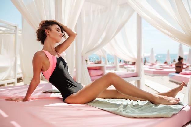 Schönes mädchen im trendigen badeanzug, der im strandzelt sitzt und verträumt die augen schließt, während sie ihr haar aufräumt. porträt der jungen nachdenklichen dame, die sich sonnt, während sie zeit am strand verbringt
