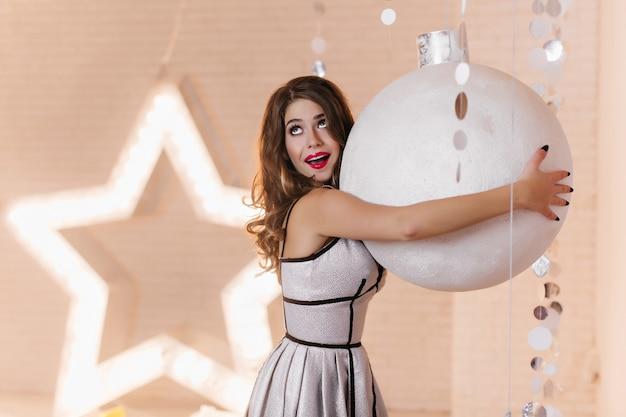 Schönes mädchen im trendigen kleid, das großes weihnachtsbaumspielzeug umarmt. innenporträt der lustigen gut gekleideten jungen frau, die auf neujahrs-fotoshooting herumalbert.