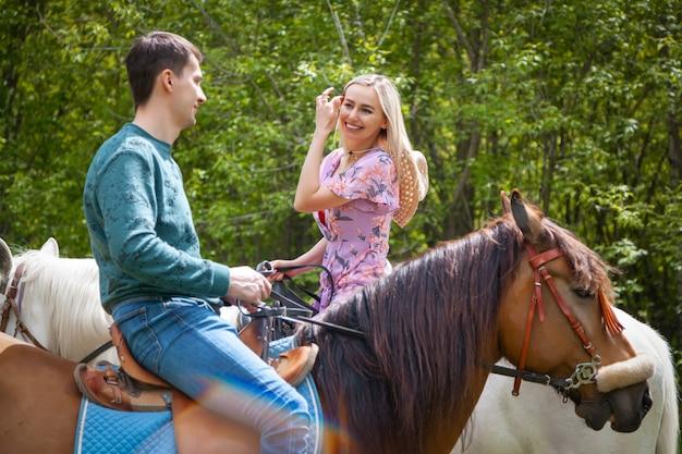 Schönes mädchen im verbindungsblumenkleid und im jungen mann, der auf pferden auf natur geht. lifestyle-stimmung. dattelliebhaber zu pferd