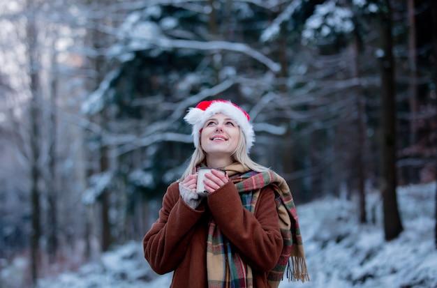 Schönes mädchen im weihnachtshut mit einer tasse in einem schneewald