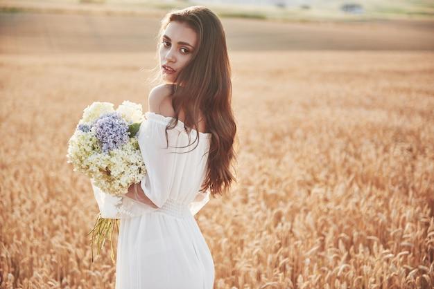 Schönes mädchen im weißen kleid, das auf dem herbstfeld des weizens zur sonnenuntergangszeit läuft.