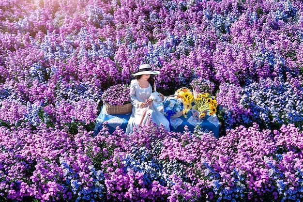 Schönes mädchen im weißen kleid, das in margaret blumenfeldern, chiang mai sitzt