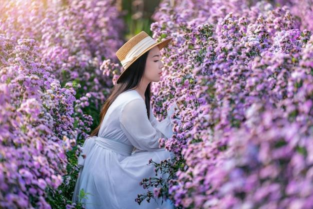 Schönes mädchen im weißen kleid, das in margaret blumenfeldern sitzt