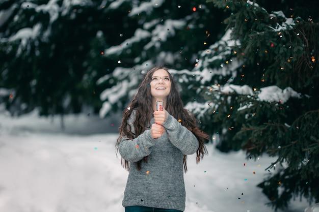 Schönes mädchen im winter in der strickjacke mit langem gebrauch petard des dunklen haares