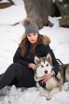 Schönes mädchen im winterwald mit hund. spielen sie mit dem hund siberian husky.