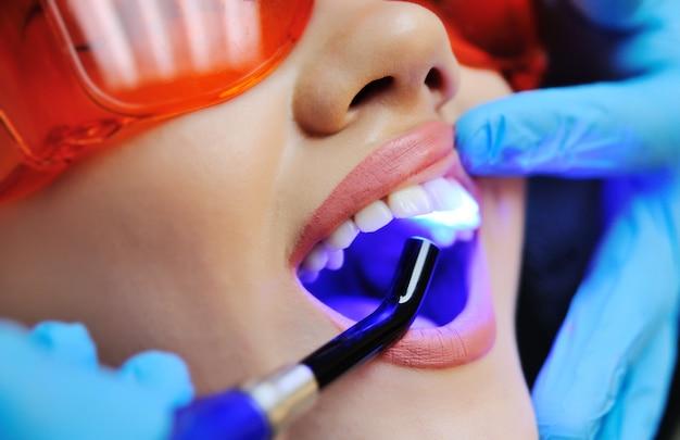 Schönes mädchen im zahnmedizinischen stuhl auf der prüfung am zahnarzt