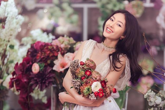 Schönes mädchen im zarten spitzenkleid mit blumenstraußblumenpfingstrosen in den händen, die gegen blumen stehen
