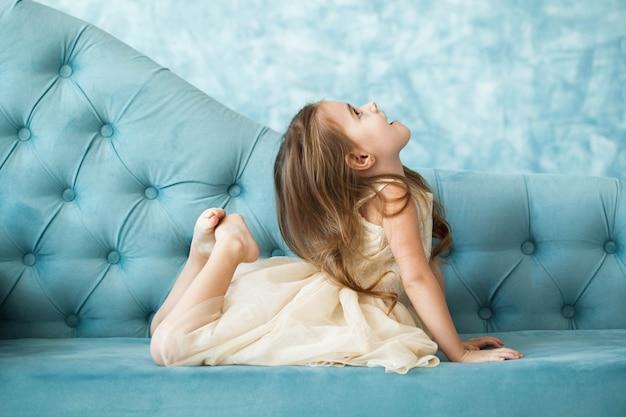 Schönes mädchen in beige kleid liegt auf blauer couch und versucht, ihren kopf mit füßen zu erreichen
