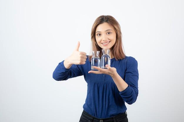 Schönes mädchen in blauer bluse, die ein glas wasser hält und daumen aufgibt.