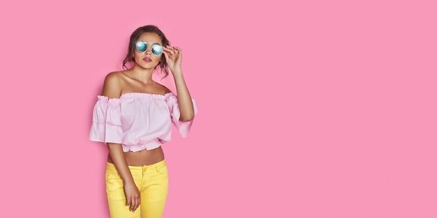 Schönes mädchen in den gelben jeans und im rosa hemd mit den händen, die sonnenbrillen tragen, die tanzend lächelnd auf rosa raum im studio aufwerfen
