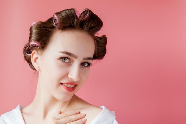 Schönes mädchen in den haarlockenwicklern auf rosa hintergrund