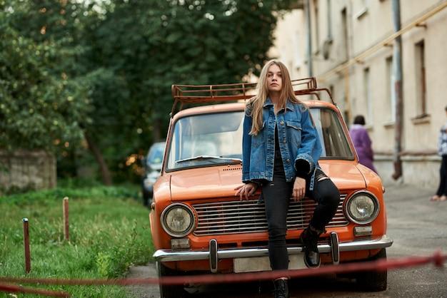 Schönes mädchen in den jeans und in einer jacke, sitzend auf der haube eines orange retro- autos.