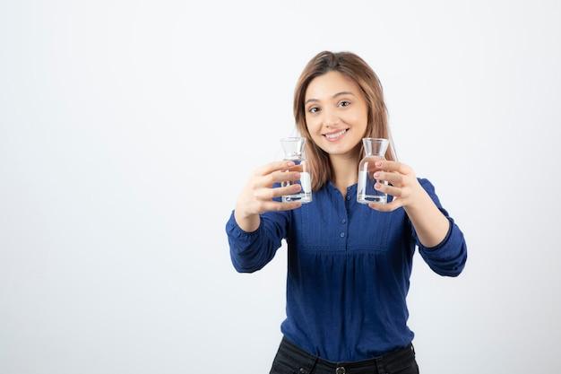 Schönes mädchen in der blauen bluse, die glas wasser auf weiß hält.