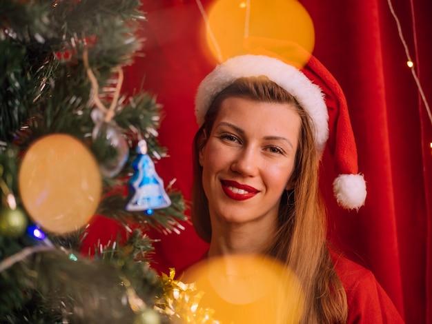 Schönes mädchen in der feiertagskleidung nahe weihnachtsbaum