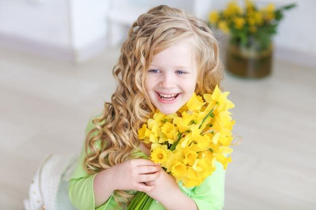 Schönes mädchen in der gelben hose in einem hellen raum mit einem strauß gelber lilien in ihren händen