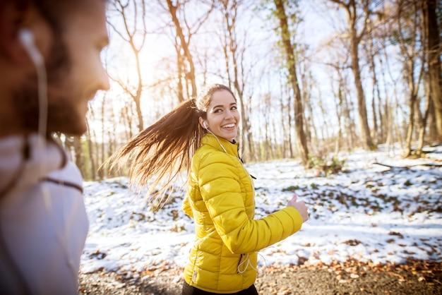 Schönes mädchen in der gelben jacke, die neben einem jungen bärtigen mann im wald mit schnee bedeckt läuft.