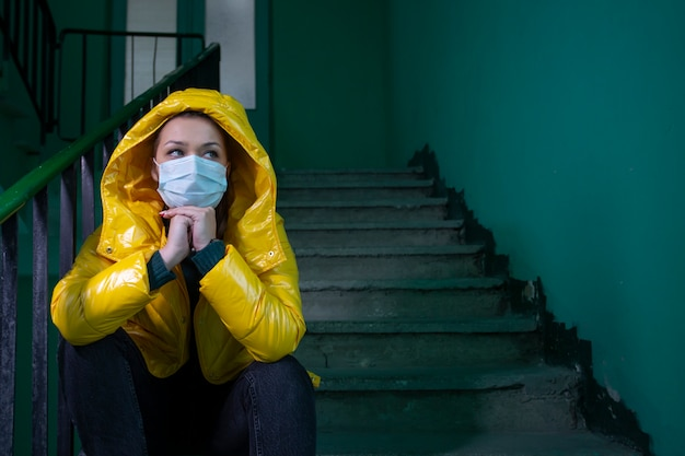Schönes mädchen in der medizinischen maske in einem isolierten verlassenen gebäude unter quarantäne gestellt