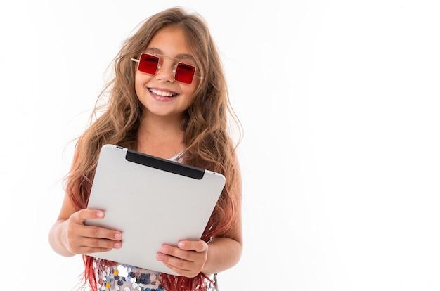 Schönes mädchen in der quadratischen roten sonnenbrille, die graue tablette hält