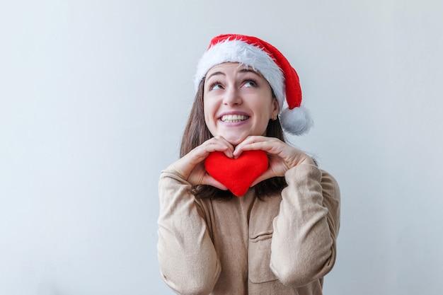 Schönes mädchen in der roten weihnachtsmannmütze, die das rote herz in der hand lokalisiert hält