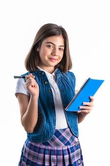 Schönes mädchen in der schuluniform mit einem notizbuch in ihrer hand auf einem weißen hintergrund.
