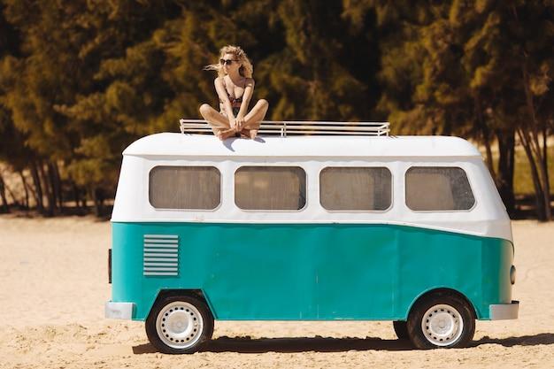 Schönes mädchen in der sonnenbrille, die oben auf hippie-bus sitzt