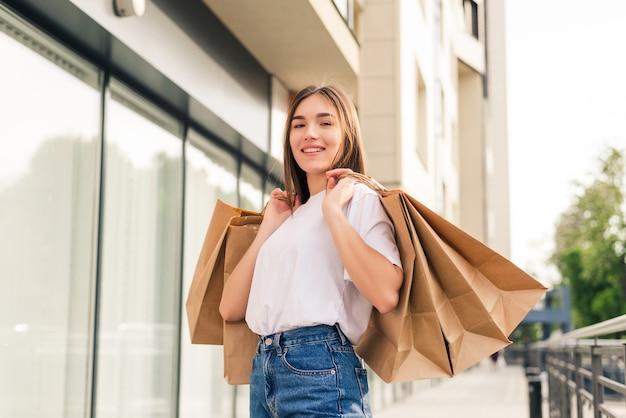 Schönes mädchen in der sonnenbrille hält einkaufstaschen und lächelt, während sie die straße entlang geht