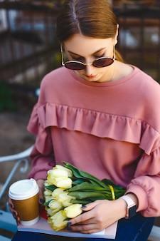 Schönes mädchen in der sonnenbrille mit einem strauß gelber tulpen, einer tasse kaffee und einer zeitschrift, die auf einer bank an einem warmen frühlingstag sitzen