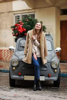Schönes mädchen in der stadt. glückliche junge frau, die nahe einem retro- auto verziert mit weihnachtsbaum steht. kalter glücklicher wintertag. feiertage, weihnachten, winter, liebe, schönheitskonzept