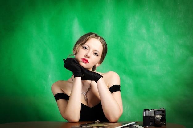 Schönes mädchen in einem abendkleid sitzt an einem tisch mit zeitschriften und einer entfernungsmesser-filmkamera