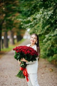 Schönes mädchen in einem anzug mit blumen in den händen einer rose auf einem grünen hintergrund