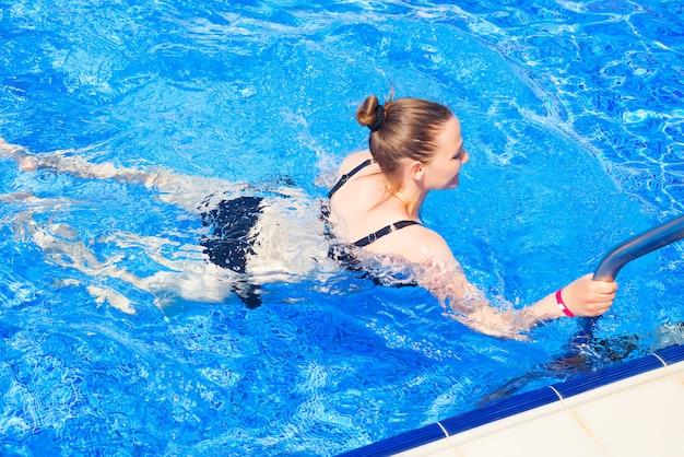 Schönes mädchen in einem badeanzug kommt in den pool. sommerurlaub