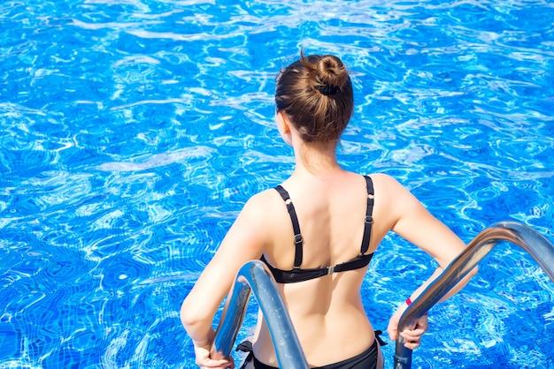 Schönes mädchen in einem badeanzug kommt in den pool