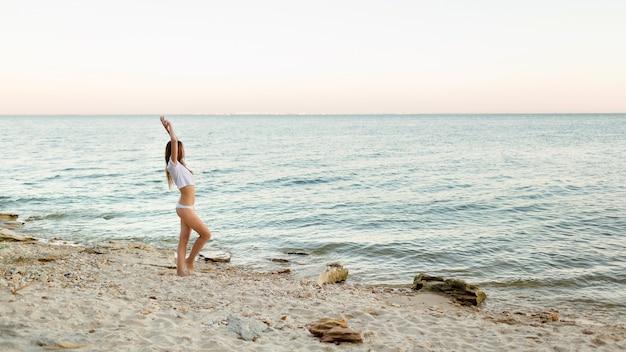 Schönes mädchen in einem badeanzug steht am strand