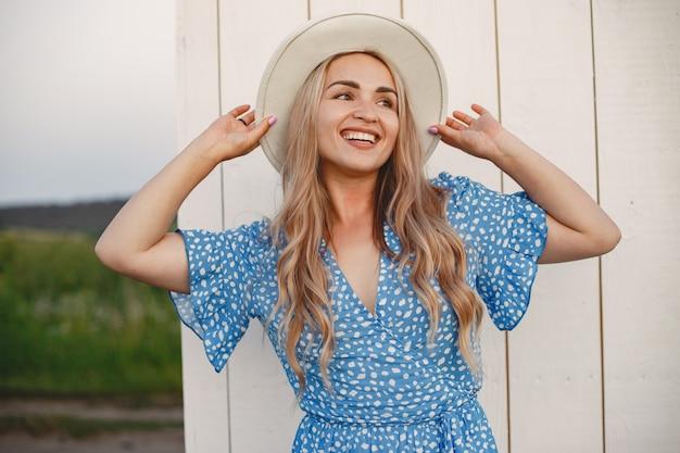 Schönes mädchen in einem blauen kleid. frau in einem sommerfeld.