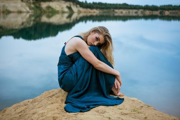Schönes mädchen in einem blauen kleid sitzt am ufer des sees trauriges, bewölktes wetter