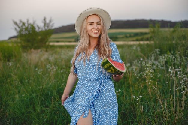 Schönes mädchen in einem blauen kleid und hut. frau in einem sommerfeld. mädchen mit einer wassermelone.