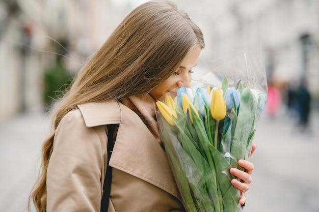 Schönes mädchen in einem braunen mantel. frau in einer frühlingsstadt. dame mit blumenstrauß