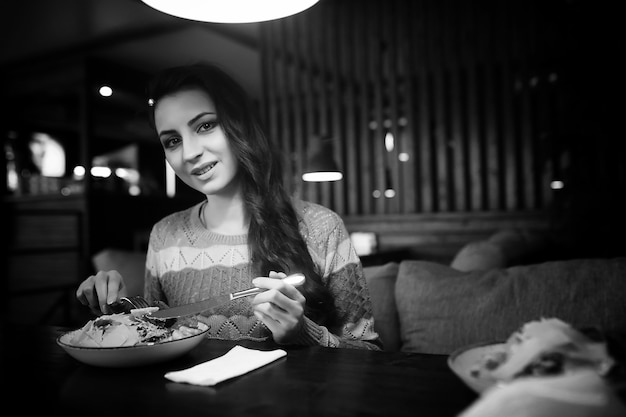 Schönes mädchen in einem café, das bei einem abendessen eine tasse kaffee trinkt