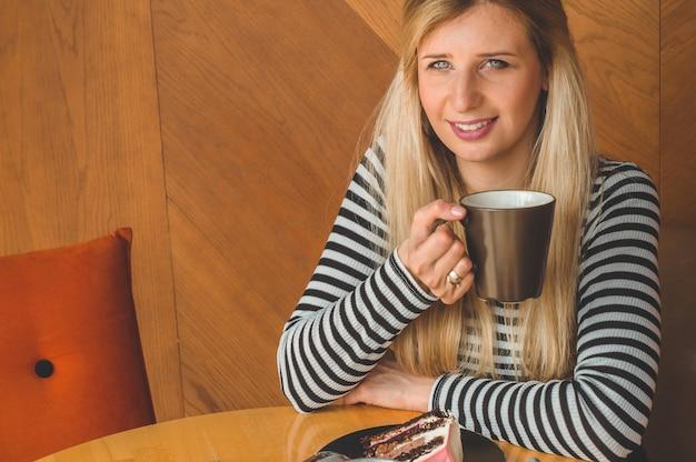 Schönes mädchen in einem café, das einen heißen tee genießt. hipster-mädchen, das heißen tee hält. erfrischungsgetränk an einem sonnigen tag.